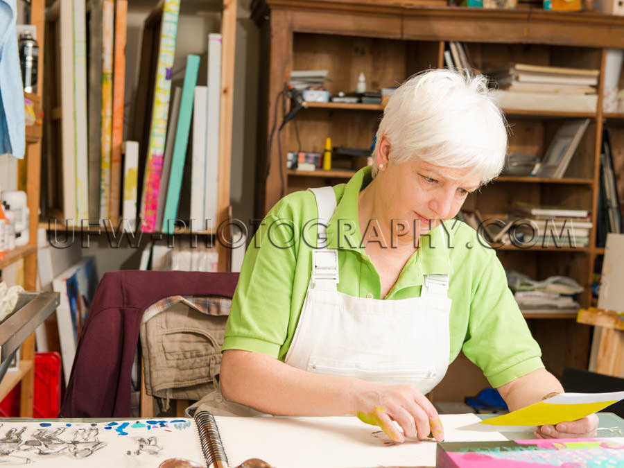 Mature woman sitting desk artist sketching art studio Stock Imag