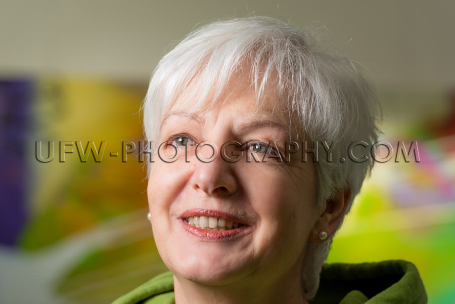 Portrait natural woman artist gray hair blurred background Stock