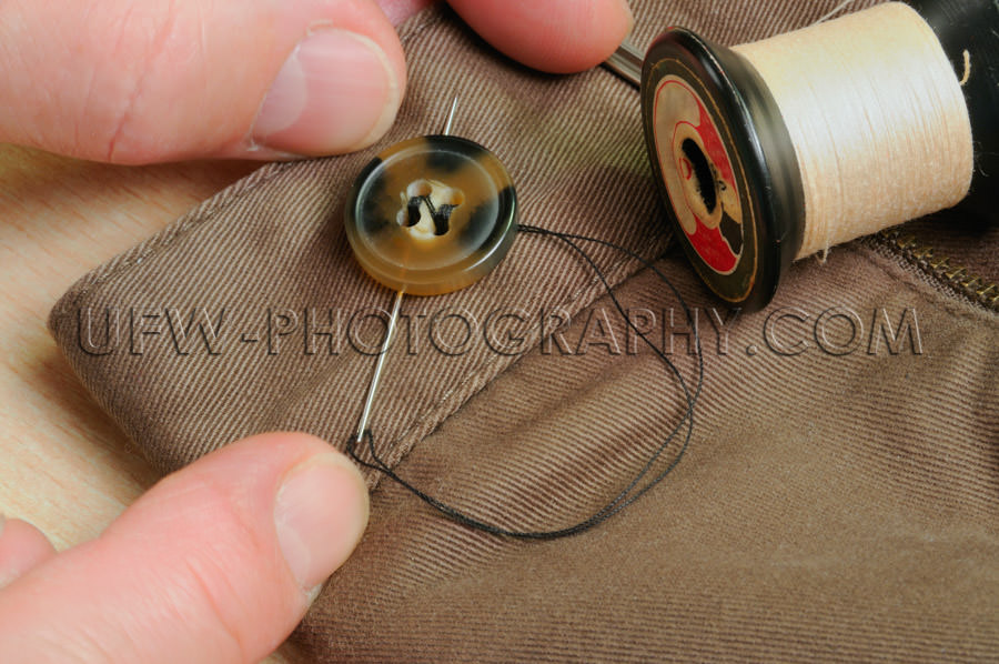 Sewing on a trouser button, macro of household chores - Stock Im