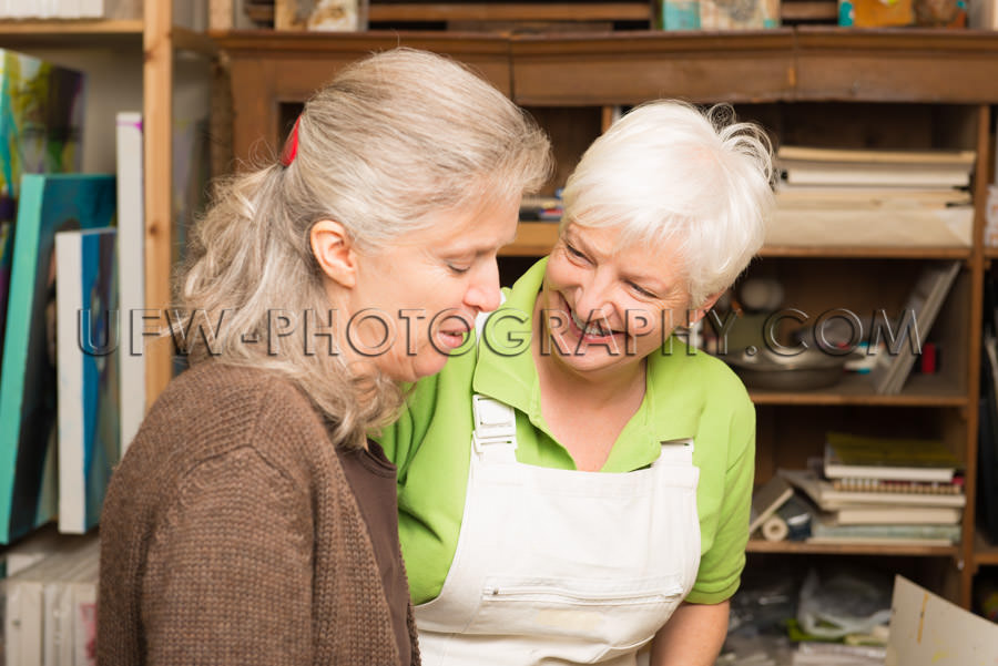 Two mature women talking gray hair art studio Stock Image
