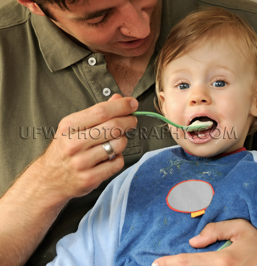 Young father caring feeding one-year-old eating child spoon mout