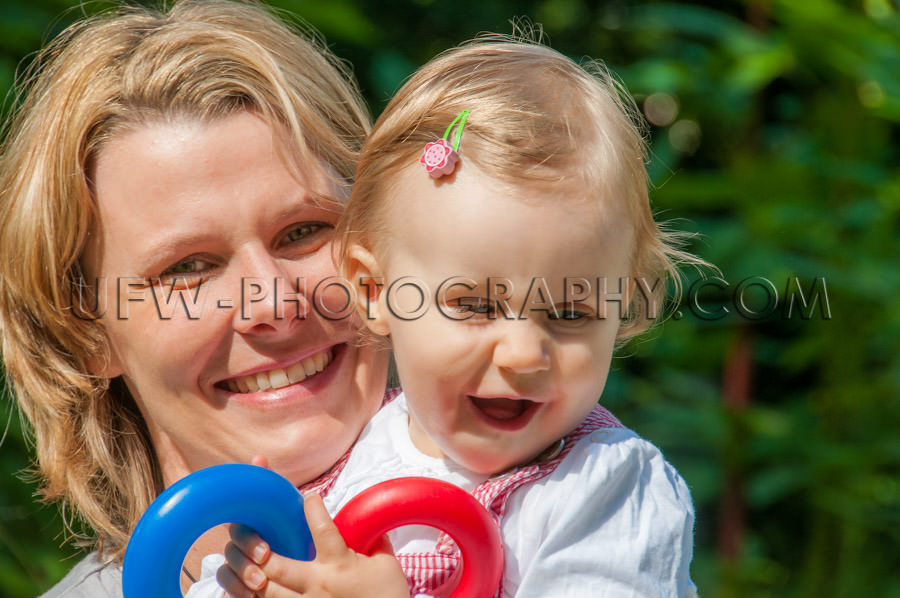 Young mother holding toddler girl happy laughing playful garden