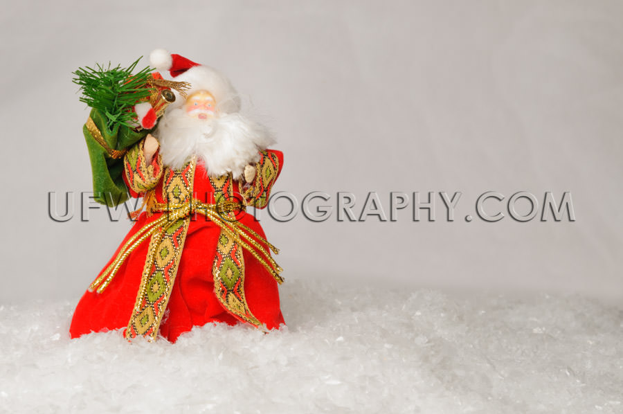Joyful Santa puppet standing fake snow red coat white beard Stoc