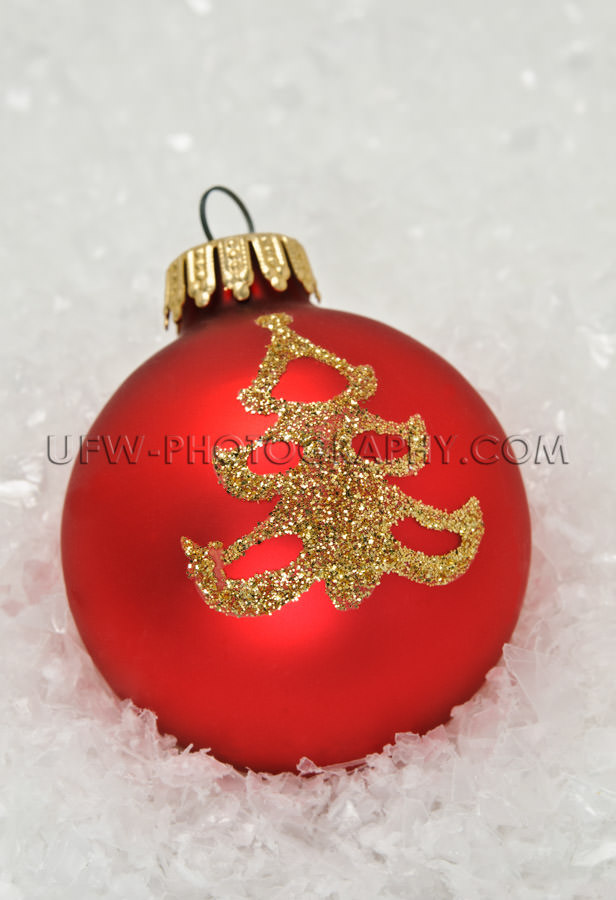 Red xmas bauble with golden tree icon, lying in snow - Stock Ima