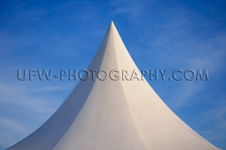 White peaked tent against deep blue sky Stock Image