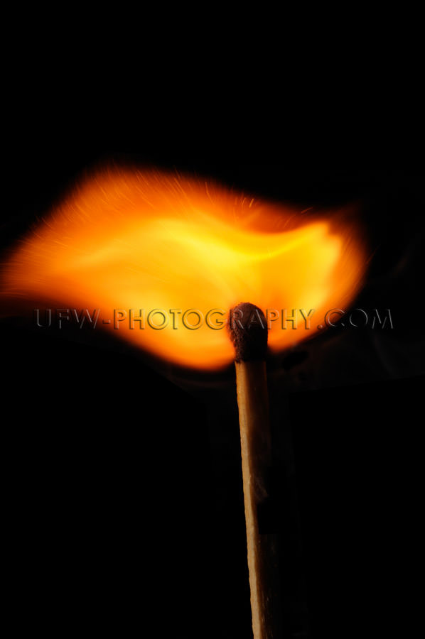 Burning matchstick emanates a beautifully shaped fire wave Stock