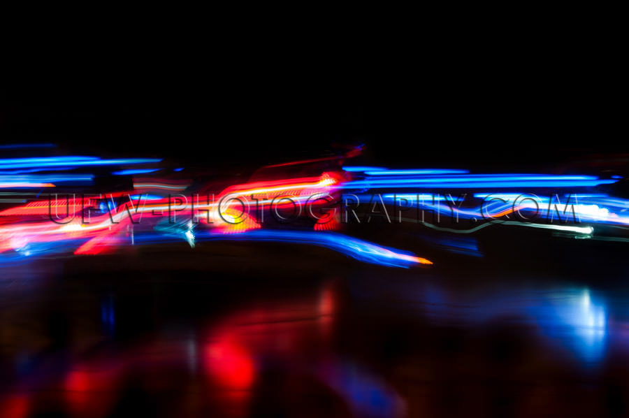 Abstract moving traffic lights red white blue motion blur black