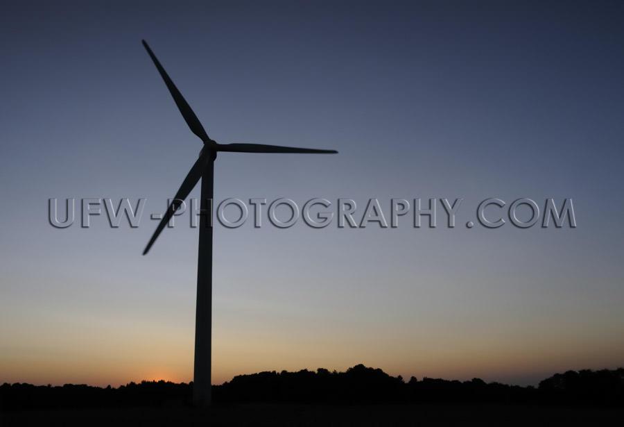 Black wind turbine silhouette, dark blue and orange night sky -
