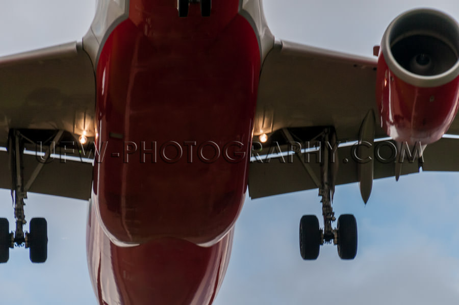 Airplane landing close-up from below silver red Stock Image