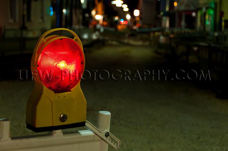 Red warning light illuminated road construction site night Stock
