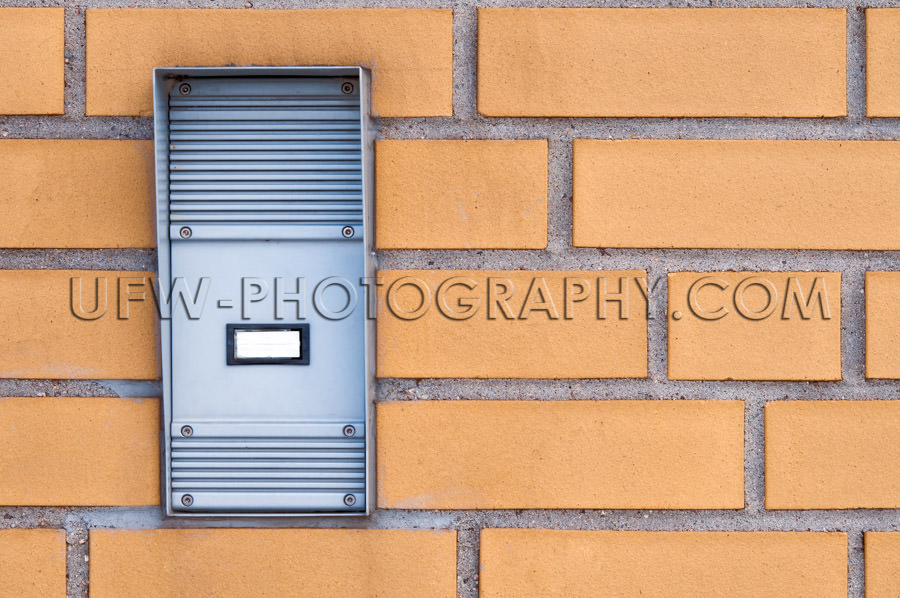 Rubust industrial door intercom, built into a yellow brick wall