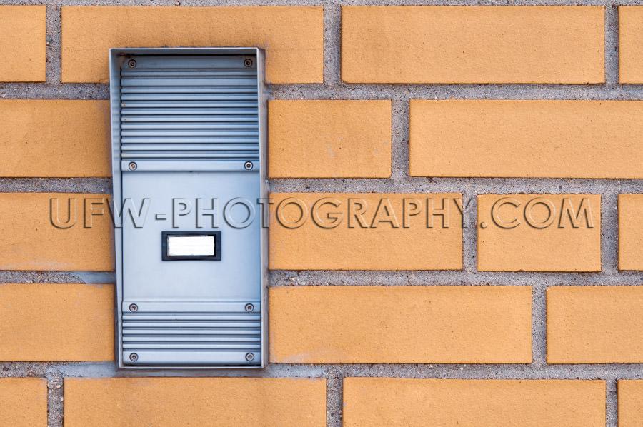Rubust industrial door intercom, built into a yellow brick wall