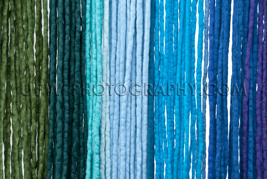 Hanging felt ribbons shades from green to blue background Stock