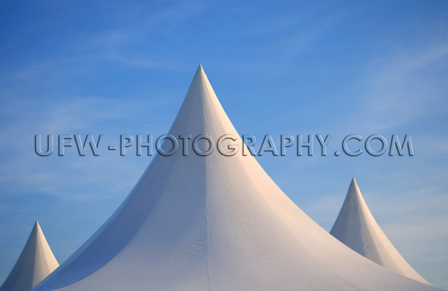 Three white spiked tent tops against deep blue sky Stock Image