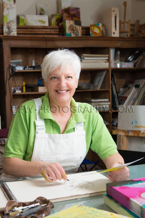 Ältere Frau Lächeln Und Zeichnen In Atelier Stock Foto