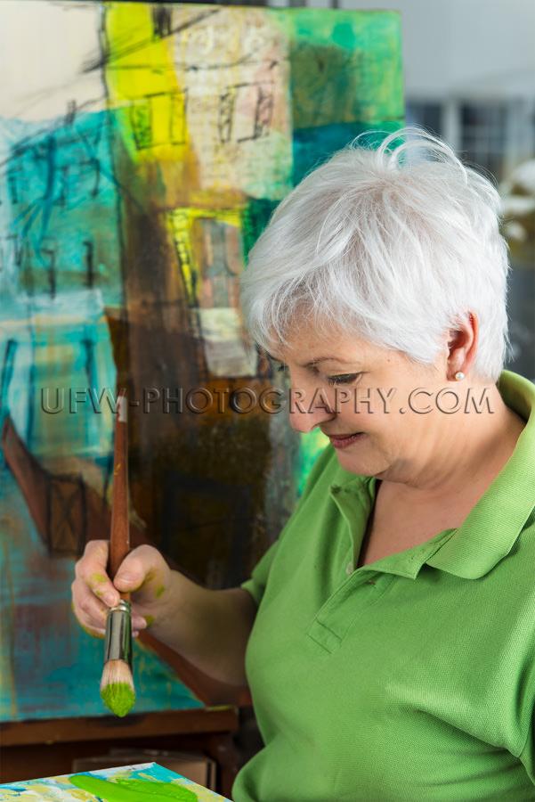 Ältere Frau trägt ein grünes T-Shirt und malt in Künstlerate