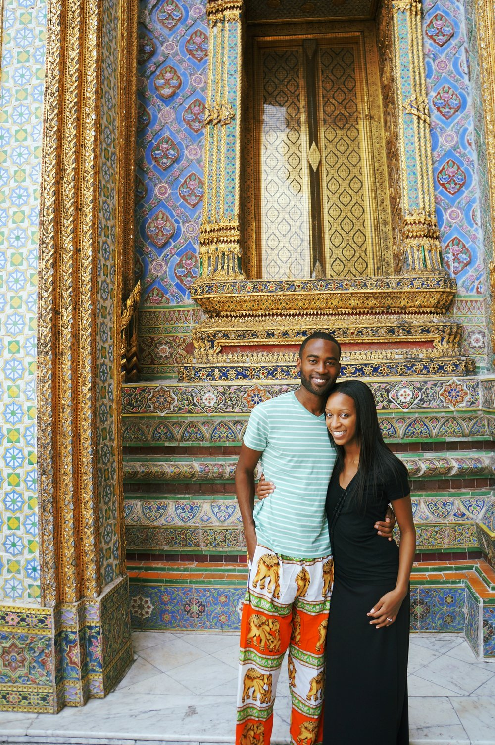 THROWBACK TO OUR FIRST INTERNATIONAL TRIP TOGETHER: THAILAND! MARQUETTE HAD TO WEAR THOSE SILLY LOANER PANTS BECAUSE HE WAS WEARING SHORTS WHICH WERE NOT ALLOWED IN THE TEMPLE. AND I HAD REALLY THIN EYEBROWS. THIS PHOTO WAS TAKEN TWO DAYS AFTER WE GOT ENGAGED!