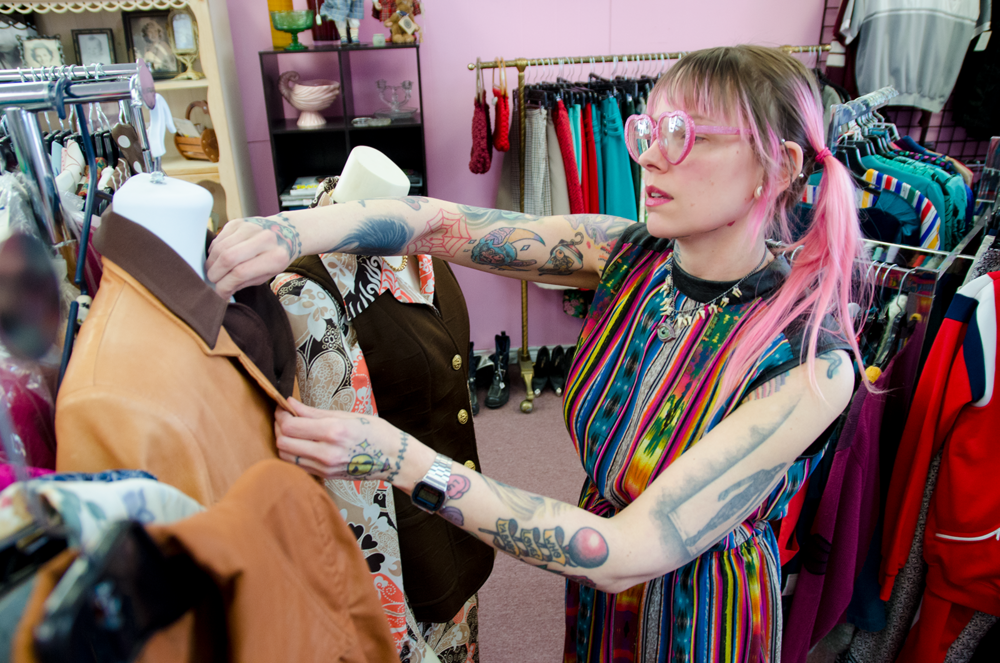 Jillian straightens a mannequin's outfit in Retro-tique's clothing room.