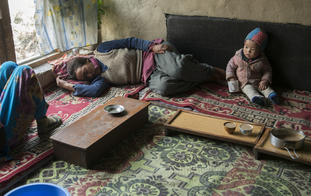 During harvest season, Soman Chasdon (center) and her daughter Lobzang Tsamo take a power nap in their home in Kumik while Chasdon's grandson Stanzon Stobgaoi plays by himself. The family has to sometimes hire Nepalese migrant workers to help with farm chores because there aren't enough people in the household to help. Two of Chasdon's older sons have left the village to pursue college education while her youngest son is a lama at the Stongde Monastery. Chasdon along with her husband and her three daughters now bear the responsibility to farm and raise the livestock.