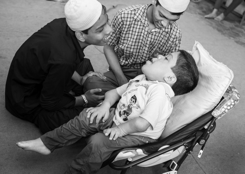 Zaid (right), 14, chats with his friends Mannan (left) and Shifaan (center) during a break at the Chingari Rehabilitation Centre in Bhopal, India. Zaid was diagnosed with Mucopolysaccharidosis Mongolism at birth. He has been receiving therapy at the Chingari Rehabilitation Centre since 2011.
