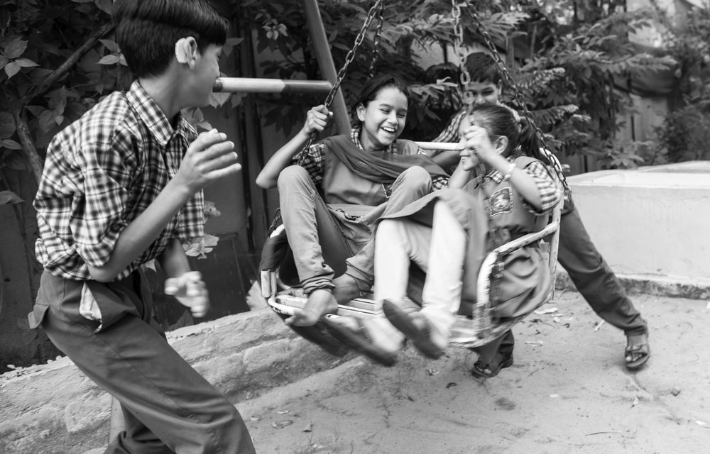 Ankit Kureen (left) and Tarun Verma (right) push a swing carrying classmates Sabia (left) and Alisha Bano (right), in the play area of Chingari Rehabilitation Centre, Bhopal, India. All four are going through therapy to align their hearing and speech skills at the Chingari Rehabilitation Centre in Bhopal, India. Their disabilities were likely caused due to their parent's exposure to MIC gas leak during the 1983 gas leak disaster