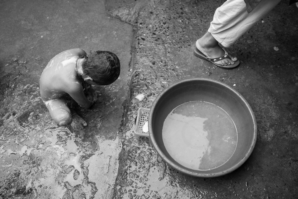 A hearing and speech impaired woman bathes a boy in Qazi Camp, a neighborhood adjacent to the abandoned UCIL plant in Bhopal, India. The groundwater in the vicinity is considered carcinogenic and mutagenic due to toxic releases from the former operations and abandonment of the UCIL factory. Clean water supply provided by the government is often intermittent and inadequate, forcing the people to use toxic groundwater from hand pumps for bathing and washing.