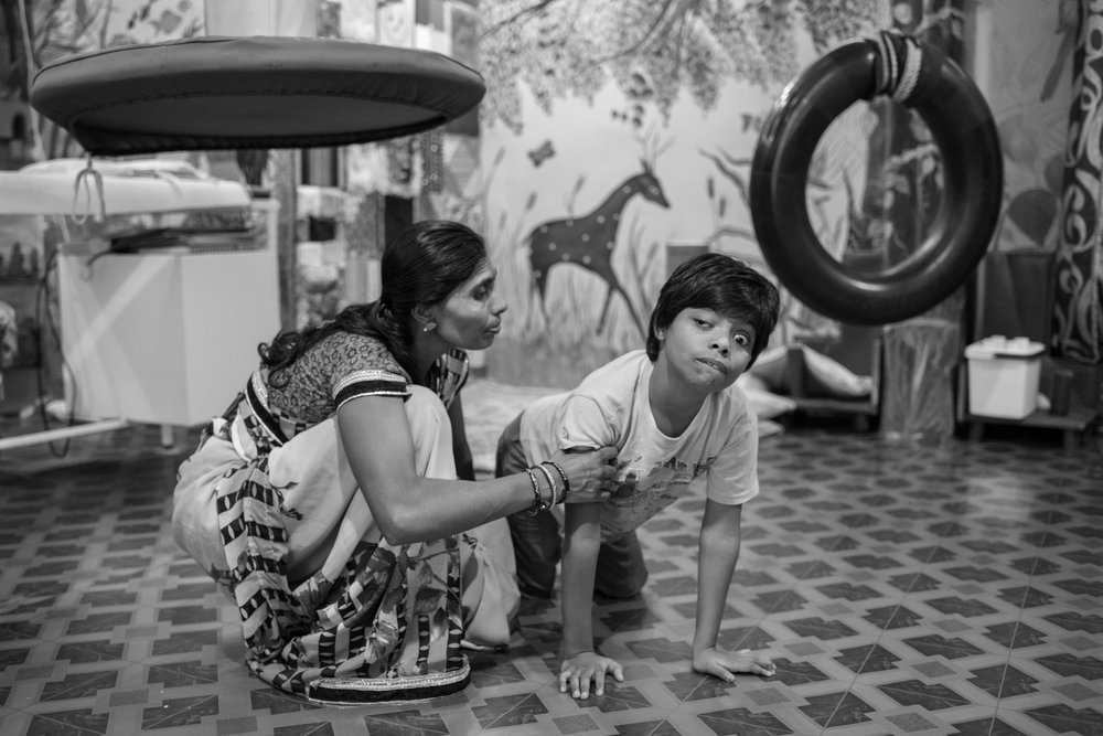Manisha Ahirwar, 10 (right), crawls besides her mother Manju Ahirwar during a physical therapy session at the Chingari Rehabilitation Centre in Bhopal, India. Manisha is both physical and psychologically disabled. While Manju was pregnant with Manisha, the family moved to a neighborhood outside the defunct UCIL facility .  Consumption of contaminated groundwater during pregnancy resulted in her daughter being born with disabilities.