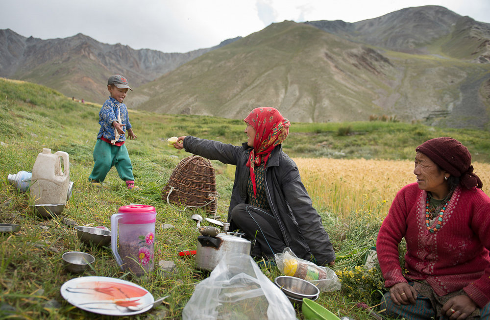 Lobzang Tsamo (center) and her mother Sonam Chasdon (right) interact with a kid from the village during lunch break at their farm in the village of Kumik in Zanskar, Kashmir. Since young men have moved away for education, families living in the village have to hire Nepalese migrant workers to help with farm chores. Over 1,000 visiting migrant workers come to Zanskar region each year, during summer. Many in Zanskar view the Nepalese migrant community as a threat to their culture preservation.