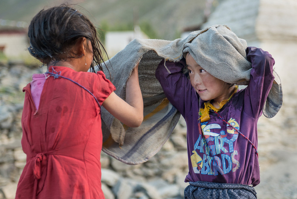 Stanzin Dasal (right) and Sonam Dolma (left) share a towel after taking a wash in Kumikthu stream in the village of Kumik in Zanskar, Kashmir. Dasal and Dolma are originally from Piptcha village but moved in with their extended families in Kumik to enroll as first graders at the Lamdon Model School. They walk approximately 4-miles each day to the village of Stongday to attend school and spend their evenings fetching water and running chores for their host families.