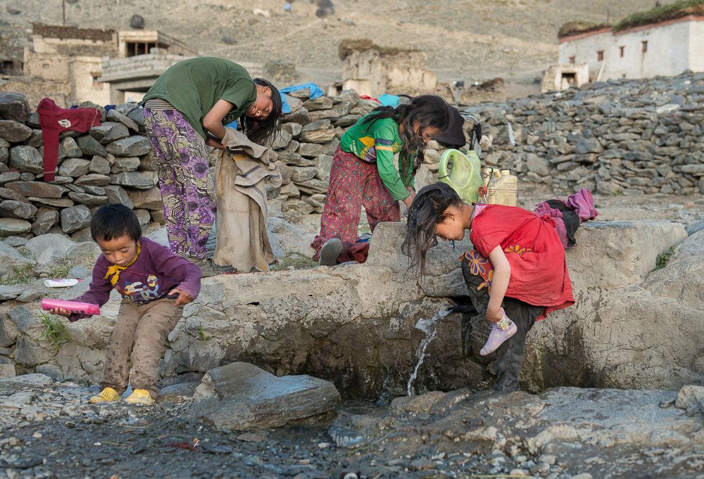 Stanzin Dasal (from left), Tenzing Chozin, Stanzin Angmo and Sonam Dolma (right) shower in the trickle of Kumikthu stream, in the village of Kumik, in Zanskar, Kashmir. During warmer months, the Sultan Largo Glacier and the surrounding snowfields that provide water to the village recede, causing water scarcity. A household in Kumik is compelled to use approximately 10-15 gallons of water a day (indoors) as compared to 400 gallons of water used per day in an American household of the same size.