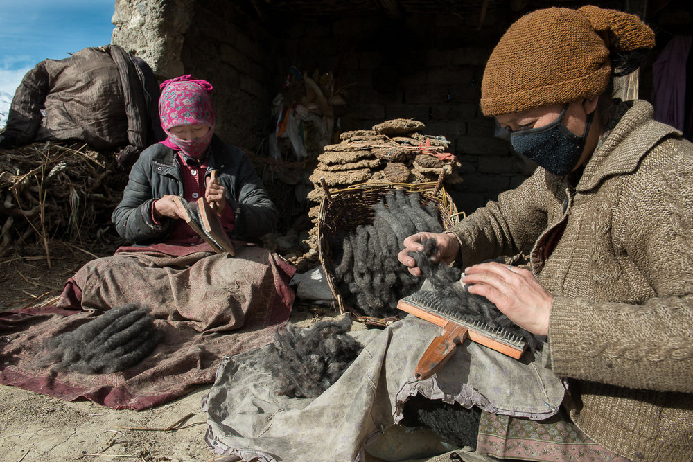 "On an unusually warm winter day in January, Lobzang Tsamo (right) and Tenzing Chazon (left) hand card wool sitting on the rooftop of their home in Kumik, in Zanskar, Kashmir. Tsamo said, ""When I was a kid, winters were so cold and snowy that we rarely came to the rooftop."""