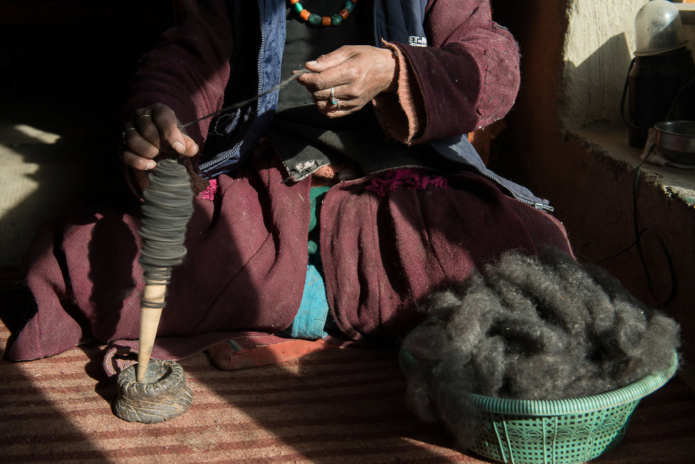 Soman Chasdon spins wool using a traditional Tibetan hand spindle at her home in the village of Kumik, in Zanskar, Kashmir. Every household in the village raises sheep for wool. Women in the village spend their time in winter carding, spinning and weaving woolen coats called Goncha.