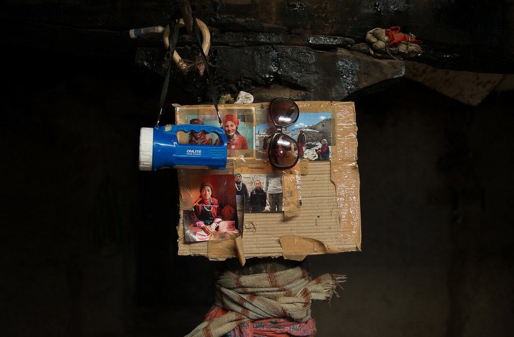 A flashlight, sunglasses and scarves hang next to family portraits of Sonam Chasdon in the village of Kumik in Zanskar, Kashmir. Chasdon uses the gear when she works at the high altitude cattle herding camp called Dhoksa. Women from the village work in a coop system by taking turns to run the Dhoksa