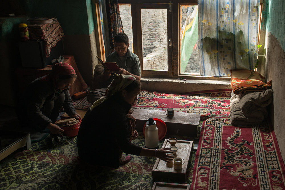 Stanzin Dayskon serves tea while her sister Lobzang Tsamo readies bread for brunch at their home in the village of Kumik in Zanskar, Kashmir. Many homes in the village, including Dayskon's, have adapted CNG gas stoves for cooking. They help improve indoor air quality and reduce emission of soot that contributes to global warming. A vast majority of homes in the region use them only to make soups or tea because CNG cylinders are cost prohibitive and many do not have the means to transport them.