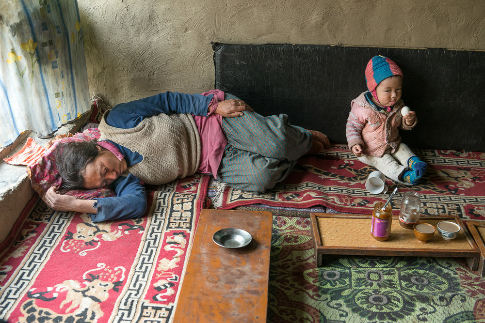 After a long day of harvest, 52-year old Soman Chasdon takes a power nap at her home in Kumik, in Zanskar, Kashmir, while Chasdon's one-year-old grandson Stanzin Stobgaoi plays with an unpeeled boiled egg. The family sometimes has to hire Nepalese migrant workers to help with farm chores because Chasdon's three sons have moved away to seek education. She, her husband and her three daughters now bear the responsibility to raise the children, work the farm and rear livestock.