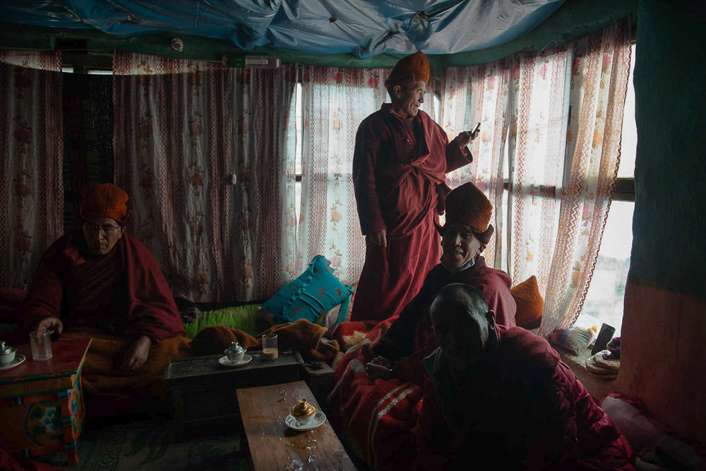 Buddhist monks from the Stongdey Monastery take a break after performing Losar prayers at a home in the village of Kumik, in Zanskar, Kashmir. The Stongdey monastery is located approximately 4 kms east of Kumik and is the second largest working monastery in Zanskar. It was established in 1052 and is dedicated to the Gelugpa school of Tibetan Buddhism. Losar is traditional Tibetan holiday that pre dates the arrival of Buddhism in Tibet.