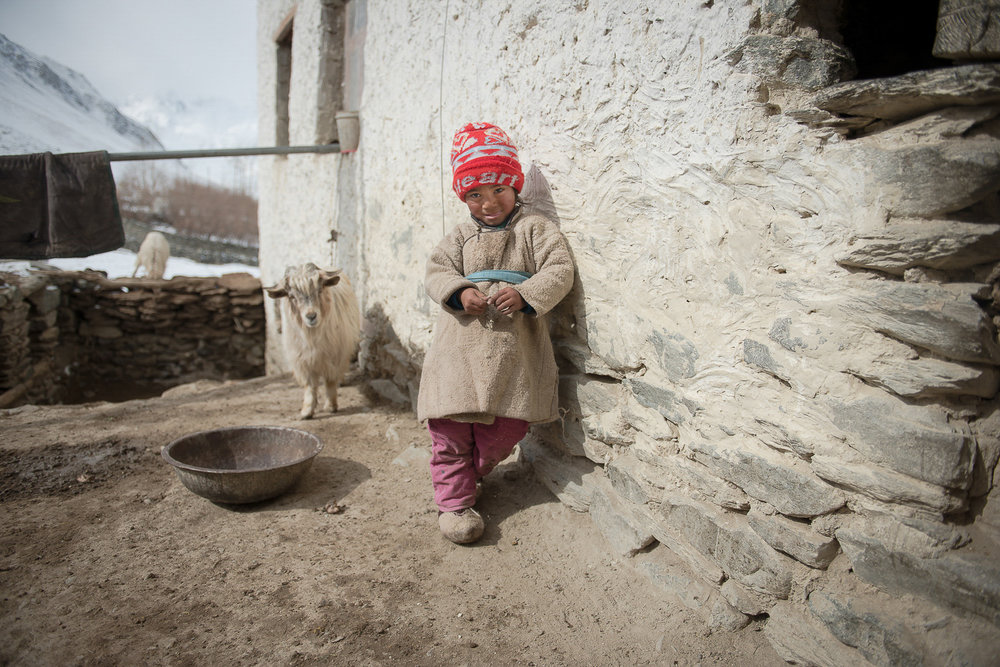 On a warm winter day, Stanzin Ignian, 3, stands in his grandparents' front porch in the village of Kumik in Zanskar, Kashmir. In the Zanskar region, winters have always been severe, with temperatures dropping to almost 40 below Fahrenheit and a snowpack that sat on the ground until June, but climate change is making winters warmer. Kumik received a scant snowfall in the 2016 winter leading to another year of water scarcity.