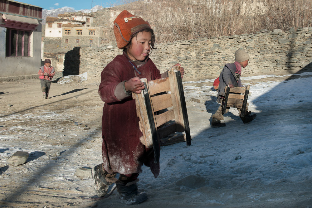 Tenzing Khando (left) and Tenzing Dala (right) attempt to play with their sledges on a small patch of snow in the village of Kumik, in Zanskar, Kashmir. The region has been receiving sparse snow in winter for the past decade, leading to a water scarcity.