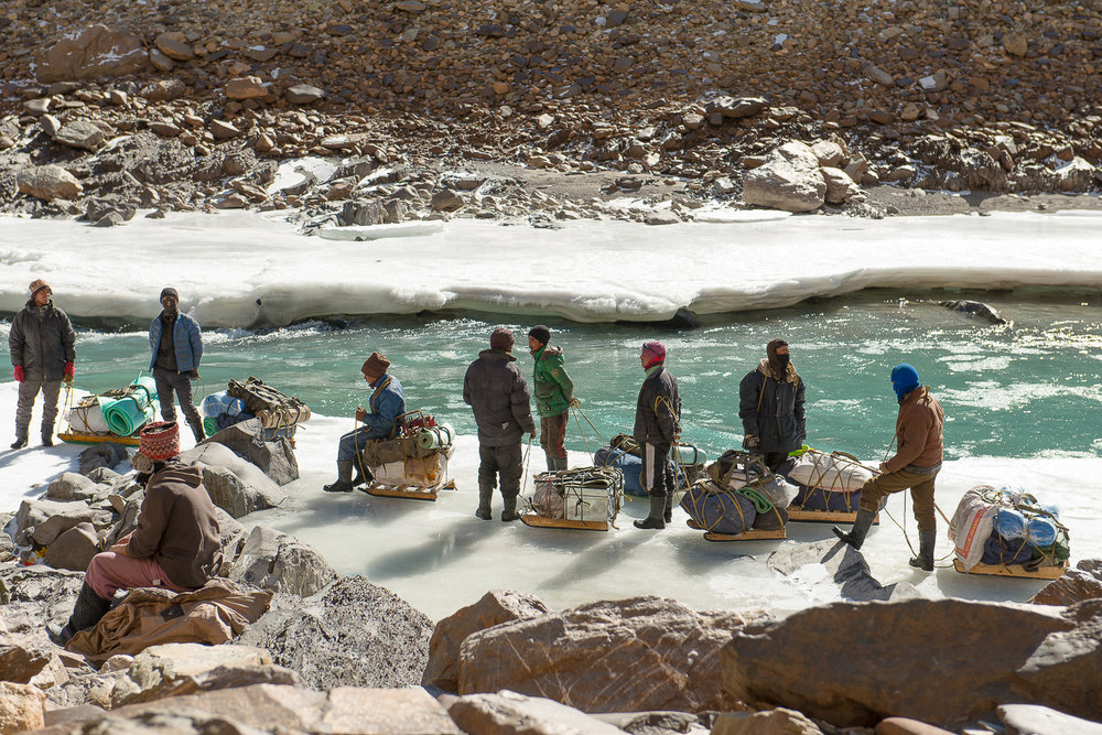 "Zanskari men take a break during their journey on the frozen Zanskar River near the village of Nerak, in Zanskar Kashmir. The Zanskar region, formerly a part of western Tibet, is a remote mountainous area in Kashmir that remains isolated from the world except in summer. The only winter '""road"" out of the valley is the frozen Zanskar River. Villagers must trek over 100 km on the frozen Zanskar, in sub-zero temperatures, at an altitude 12,000 feet, to get medical attention or to trade."