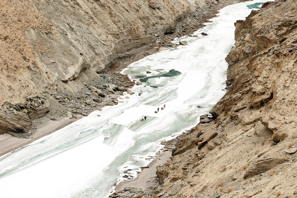 "Men walk on the frozen Zanskar River near the village of Chilling, in Zanskar, Kashmir. For centuries, the people of Zanskar have made their way out of the region for business via a 100-km frozen Zanskar river trail. The trail is a part of the ancient Silk Route and is called the Chadar, which means ""veil of ice."" Climate change is resulting in warmer winter temperatures, due to which the river does not freeze completely, making this journey treacherous and life threatening."