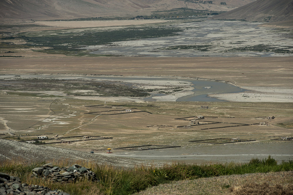 A view of the village of Kumik Martang captured from the village of Kumik in Zanskar, Kashmir. Kumik has been facing a water crisis for over a decade due climate change, forcing villagers to abandon their ancestral village and build a new village named Kumik Martang near the Tsarap River. By 2014, seven of the 35 families relocated to the new village and began farming. But a devastating flood caused by the Tsarap River in spring 2015 destroyed the canals and farmlands in the new village.