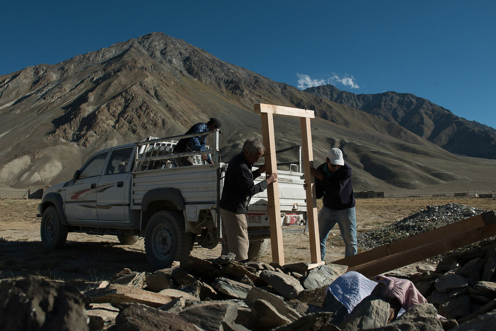 Nawang Punchok (left) and Thinley (right) resident of the village of Kumik drop off a doorframe at a home that is under construction in Kumik Martang in Zanskar, Kashmir. Despite knowing that the 2015 flashflood destroyed the newly built village and left it waterless, a few families from the old village of Kumik are continuing to construct homes in the new village.