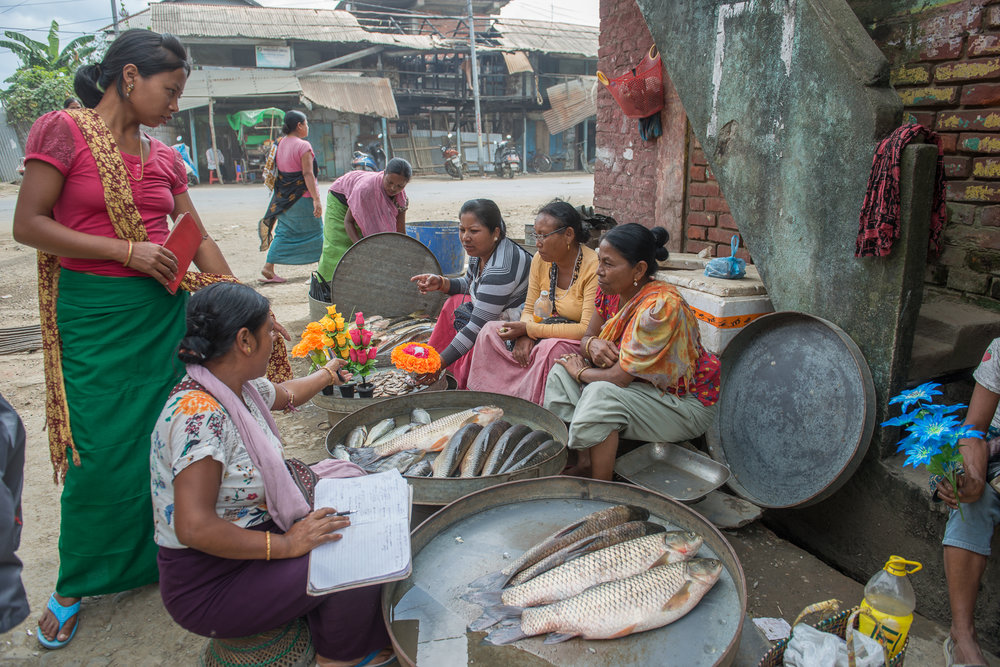 Fisherwomen and vegetable vendors wrap up business for the day in the Ema market in Ningthoukhong, in Manipur. Recurrent floods during monsoon season in 2017 impacted fisheries and vegetable harvest in the area
