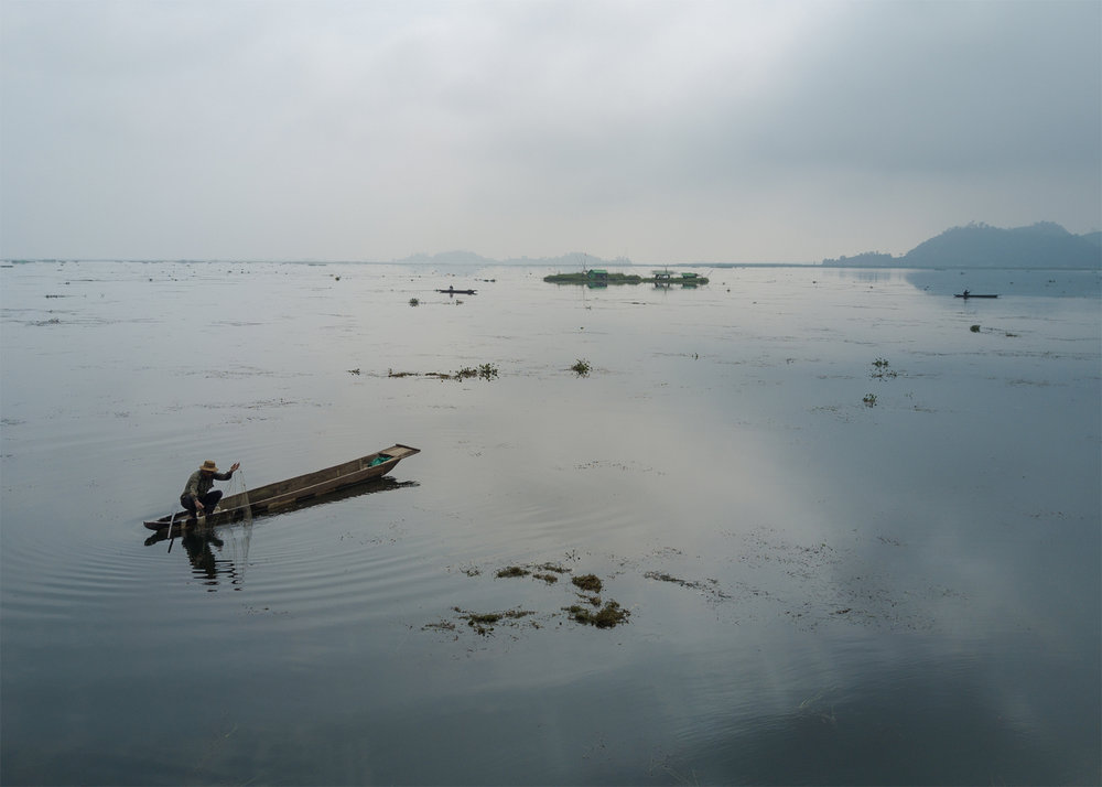 A Meitie fisherman fishes near phumshangs (floating huts) in Loktak Lake, Manipur. The construction of the Ithai Dam flooded over 80,000 hectares of farm and pasture land in the vicinity of the Loktak wetland. The Loktak Development Authority has been dredging the phumdis (floating biomass) and has cleared over 800 Phumshangs in the name of lake clean-up for efficient power generation.