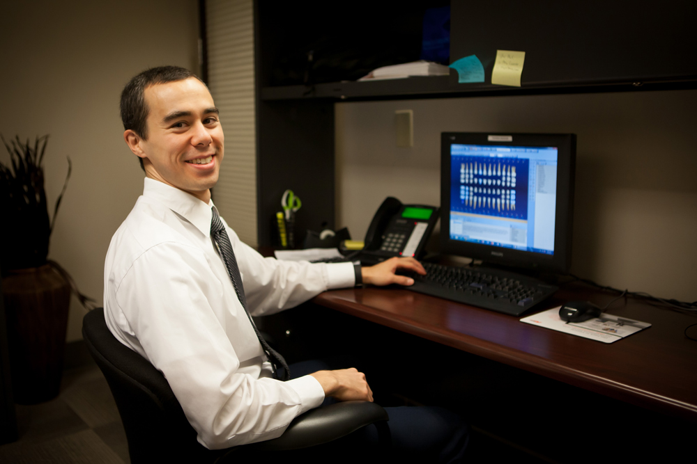 Dr. Kevin Suzuki sitting at his desk reviewing a patient file.