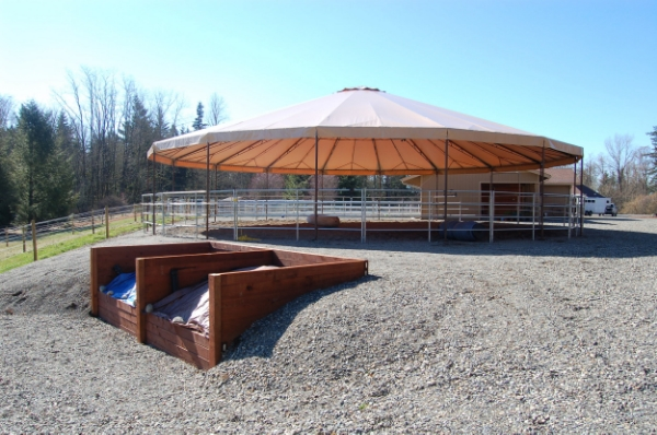 Locating a high area on your property for your arena or round pen location, like the owners of this covered round pen have done, will help ensure you do not have issues with run-off coming in and making your footing unusable.