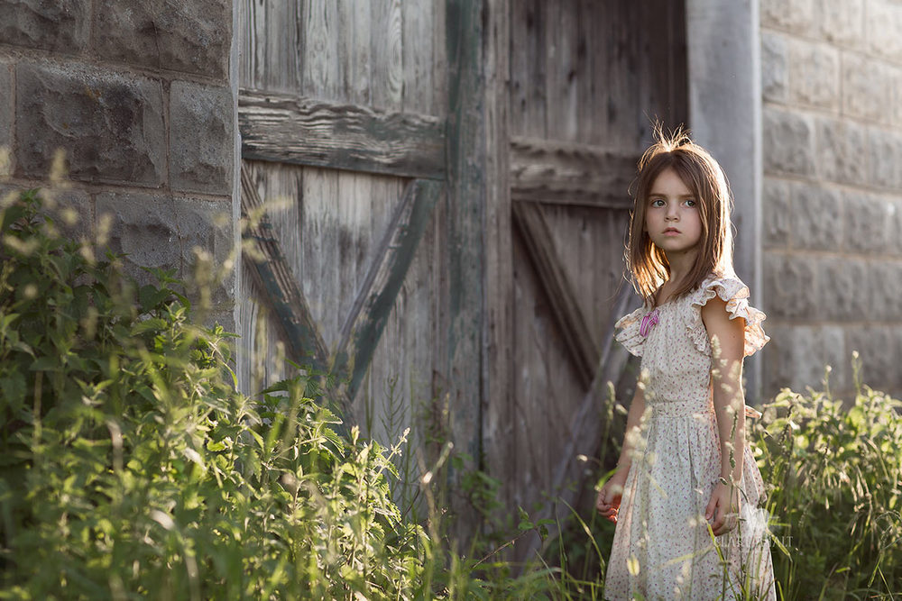 Portrait of a child near old farm buildings.  Photographed in Frederick, MD by Clare Ahalt Photography