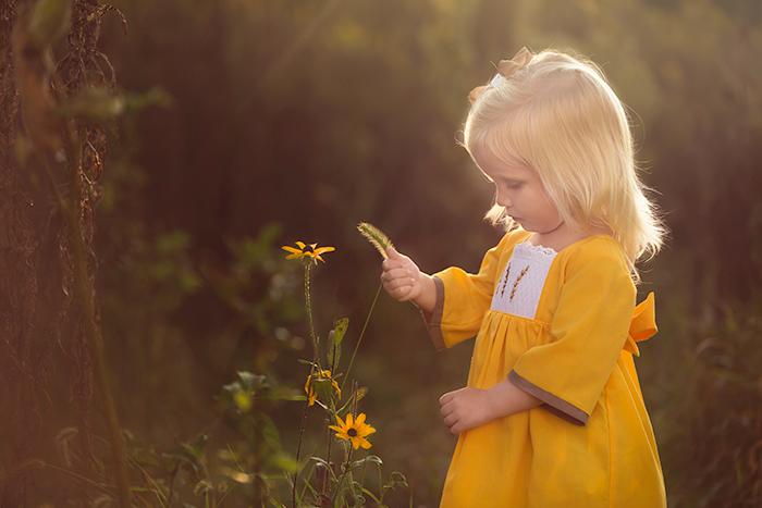 Portrait of a little girl in a yellow dress picking a black eyed susan flower in Maryland.  Photographed by Clare Ahalt, a professional fine art portrait photographer located in mid-maryland, specializing in fine art child portraiture and high school senior portraits