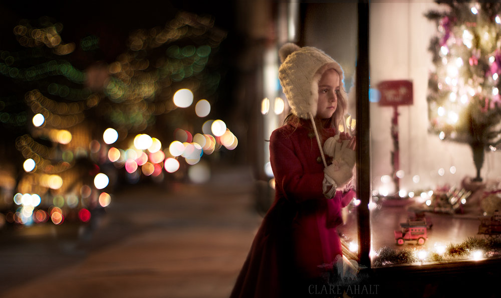 portrait of a little girl outside a shop window, photographed in downtown frederick by Clare Ahalt Photography, a fine art portrait photographer located in Maryland.