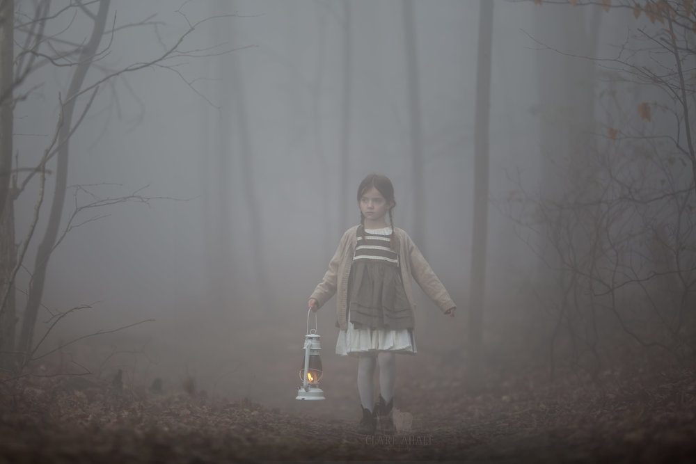 portrait of a child alone in the woods with a lantern on a foggy night taken on location in Maryland by Clare Ahalt Photography, a fine art portrait photographer located in Mid-maryland, photographing on location in Maryland, Northern Virginia and Washington DC.  Available for destination photography